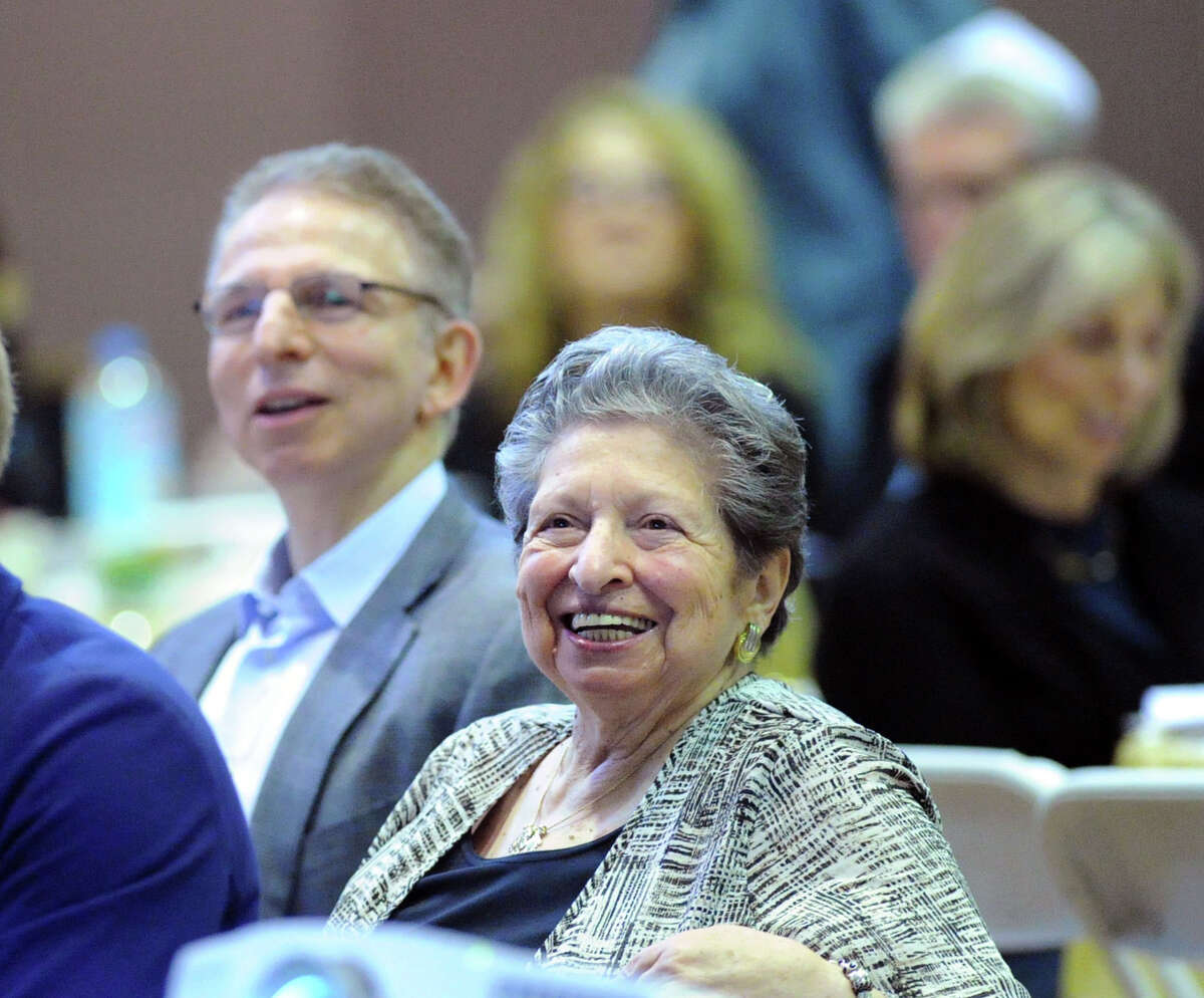At center, Rita Katcher smiles during the Sholom Center Passover Seder at Temple Sholom in Greenwich, Conn., Friday night, April 3, 2015.