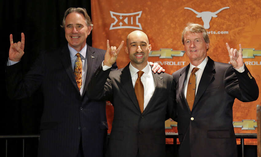 The University of Texas at Austin men's athletic director Steve Patterson (left) and University of Texas at Austin president Bill Powers (right) pose for photos with new men's basketball head coach Shaka Smart (center) during a press conference Friday April 3, 2015 at the Frank Erwin Center in Austin, TX.