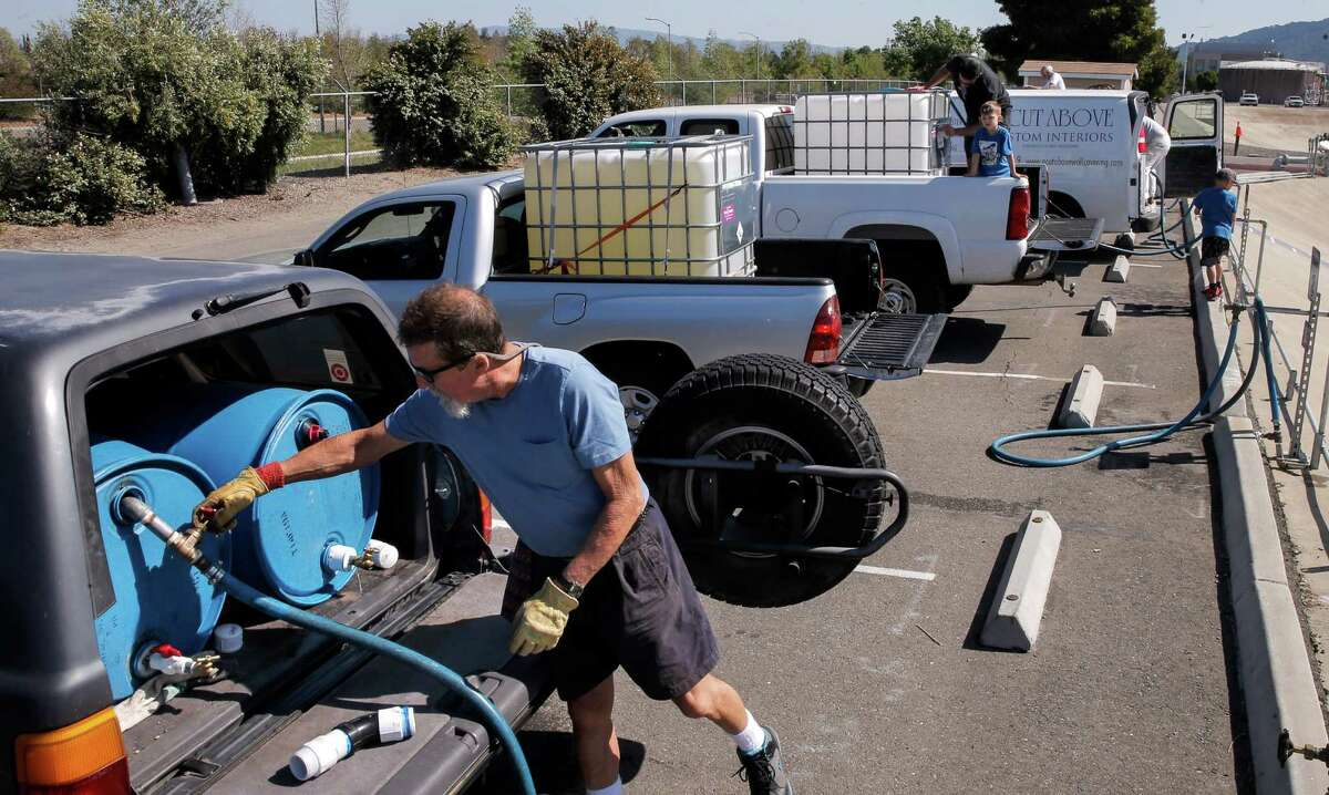 Steve London joins a line of vehicles as they fill their containers with recycled water at the Dublin San Ramon Services District Recycled Water Plant in Pleasanton, Calif., as seen on Fri. April 3, 2015.