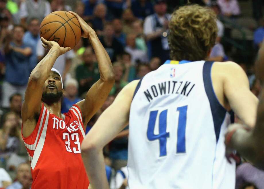 DALLAS, TX - APRIL 02:  Corey Brewer #33 of the Houston Rockets takes a shot against Dirk Nowitzki #41 of the Dallas Mavericks at American Airlines Center on April 2, 2015 in Dallas, Texas.  NOTE TO USER: User expressly acknowledges and agrees that, by downloading and or using this photograph, User is consenting to the terms and conditions of the Getty Images License Agreement.  (Photo by Ronald Martinez/Getty Images) Photo: Ronald Martinez, Staff / 2015 Getty Images