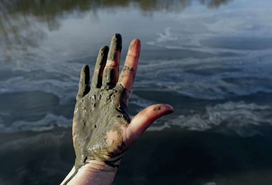 Amy Adams, an environ-mentalist, shows her hand covered with coal ash from the Dan River in North Carolina in 2014. swirling in the background as state and federal environmental officials continued their investigations of a spill of coal ash into the river in Danville, Va., Wednesday, Feb. 5, 2014. Duke Energy estimates that up to 82,000 tons of ash has been released from a break in a 48-inch storm water pipe at the Dan River Power Plant in Eden N.C. on Sunday. (AP Photo/Gerry Broome) Photo: Gerry Broome, STF / AP