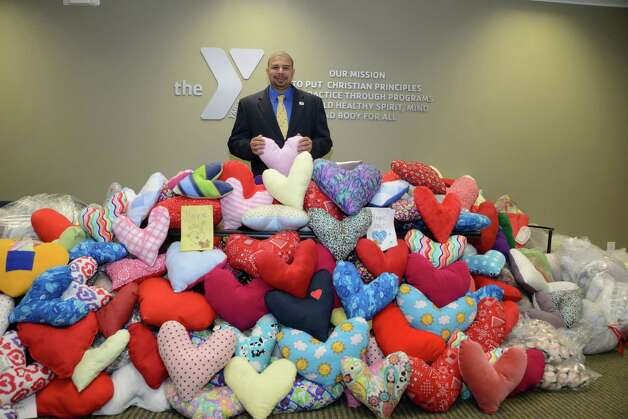David Brown, president and CEO of the Capital District YMCA is shown with some of the 600 heart pillows delivered last week to Ellis Medicine as part of the Y?s Hug-A-Heart program. The heart-shaped pillows help ease pain and aid in the post-surgery recovery of cardiac patients. They were sewn and stuffed by volunteers locally and beyond. Pillows came from dozens of youth groups, senior centers, local schools and YMCAs in Amsterdam and North Carolina. (Sumbitted by Robert Totaro)