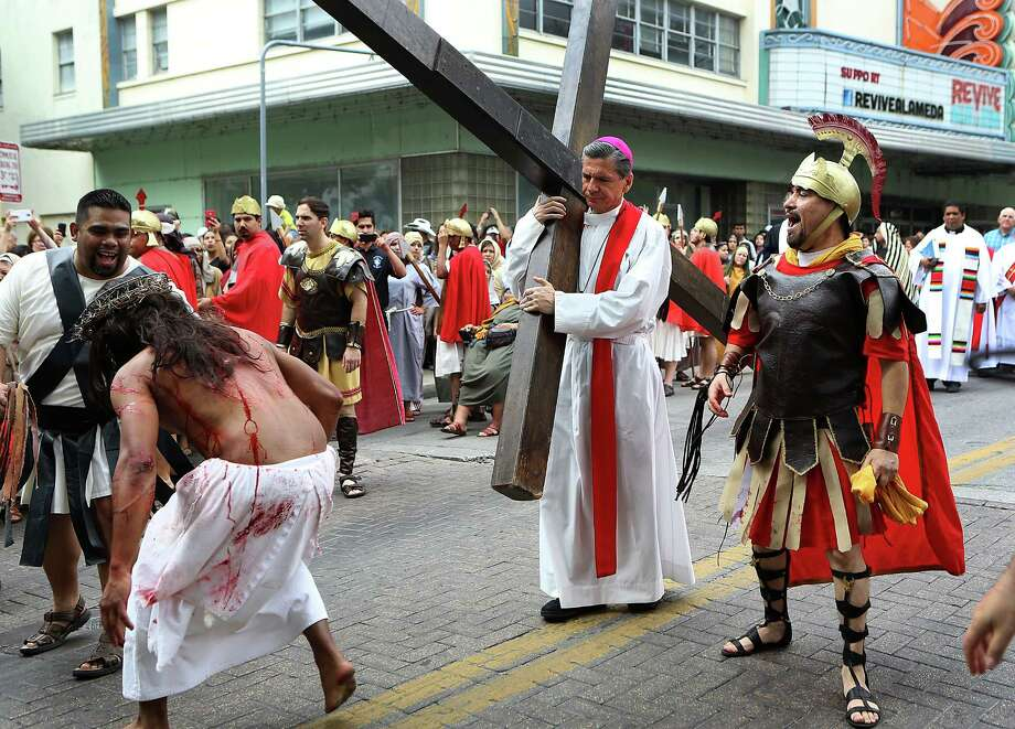 Archbishop Gustavo Garcia-Siller, center, carries the cross for Jesus a while during The Passion Play in San Antonio. The event is a San Fernando Cathedral tradition which started in 1983.  It depicts the trial, suffering and death of Jesus. Friday, April 3, 2015. Photo: Bob Owen, Staff / San Antonio Express-News / © 2015 San Antonio Express-News