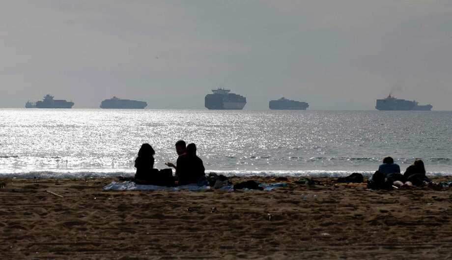 FILE - In this Feb. 20, 2015 file photo, people sit on the sand in Sunset Beach, Calif., as loaded cargo ships are anchored outside the Ports of Long Beach and Los Angeles. A tentative contract agreement that restored the flow of international trade through West Coast seaports earlier this year took a big step closer to becoming official, Friday, April 3, 2015 as representatives of the dockworkers' union overwhelmingly recommended that rank-and-file members vote to approve the deal. Difficult contract negotiations nearly closed 29 seaports from San Diego to Seattle, causing major delays in the delivery of billions of dollars of imports and exports. (AP Photo/Jae C. Hong, File) Photo: Jae C. Hong, STF / AP
