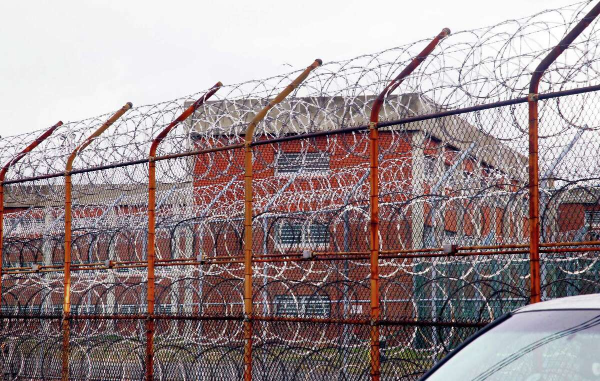 FILE - In this March 16, 2011, file photo, a security fence surrounds the inmate housing on New York's Rikers Island correctional facility in New York. The two-year study at New York?'s sprawling jail complex concluded with a bold recommendation to remove health workers entirely from the most contentious dilemma they face, whether to put an inmate in solitary. That?'s because many doctors believe the confinement, which involves 23-hour stretches of isolation, could harm inmates. (AP Photo/Bebeto Matthews, File) ORG XMIT: NYR303