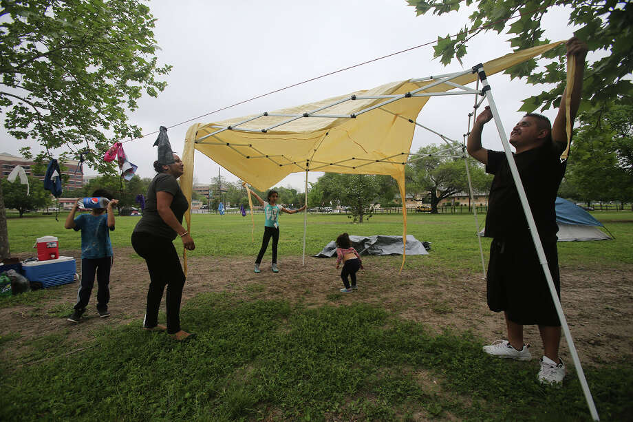 Gracie Fernandez (left) and her husband Javier Cortez (right) set up a shelter Friday April 3, 2015 for their stay at Brackenridge Park during the Easter weekend. With them are their kids Aaron Fernandez (far left), Laisha Fernandez,10, (center, blue and white shirt) and Gianna Cortez, 19 months (facing away). This is the first time this family has stayed over night at Brackenridge Park for Easter weekend. Photo: John Davenport, Staff / Brack Park