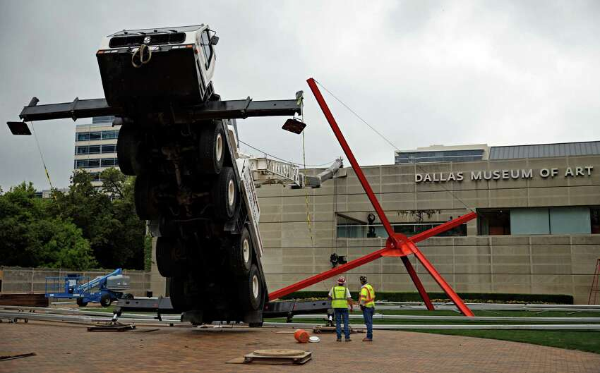 Workers look on at a collapsed crane in front of the Dallas Museum of Art, Friday, April 3, 2015 in Dallas. The truck-mounted crane has toppled onto the roof of the Dallas Museum of Art, injuring the operator and narrowly missing a sculpture outside the building.