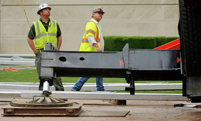 Workers look at a collapsed crane in front of the Dallas Museum of Art, Friday, April 3, 2015 in Dallas. The truck-mounted crane has toppled onto the roof of the Dallas Museum of Art, injuring the operator and narrowly missing a sculpture outside the building.