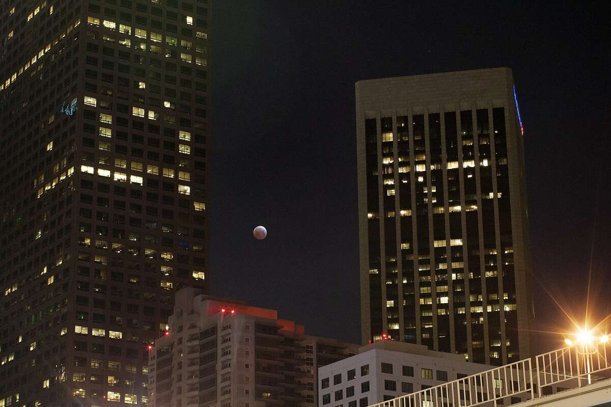 LOS ANGELES, CA - APRIL 3: The moon is seen behind downtown high-rise buildings during the shortest total lunar eclipse of the century before dawn on April 3, 2014 in Los Angeles, California. The eclipse, with the moment of totality lasting only about five minutes, is particularly brief because the moon is passing through the upper part of the Earth's circularshadow rather than across the middle, which would have made it last longer. (Photo by David McNew/Getty Images)