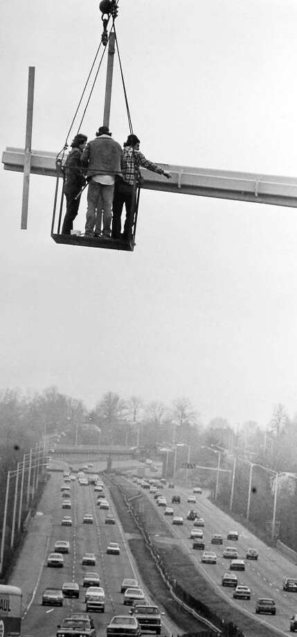 March 8. 1985: Construction workers mount braces for a sign over the Connecticut Turnpike in front of the southbound service plaza on the Darien-Stamford line. The camera angle distorted the picture slightly, the men were not as far above the highway as they appear. Photo: File Photo, File Photo/Dave Elkinson / Stamford Advocate File Photo