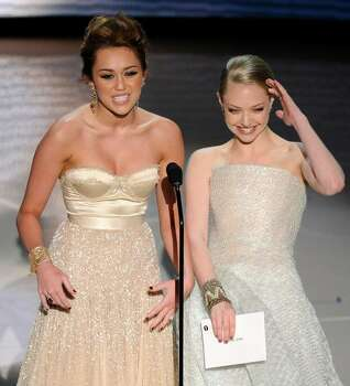 Miley Cyrus, left, and Amanda Seyfried present the best original song during the 82nd Academy Awards Sunday,  March 7, 2010, in the Hollywood section of Los Angeles. (AP Photo/Mark J. Terrill) Photo: Mark J. Terrill, AP / AP