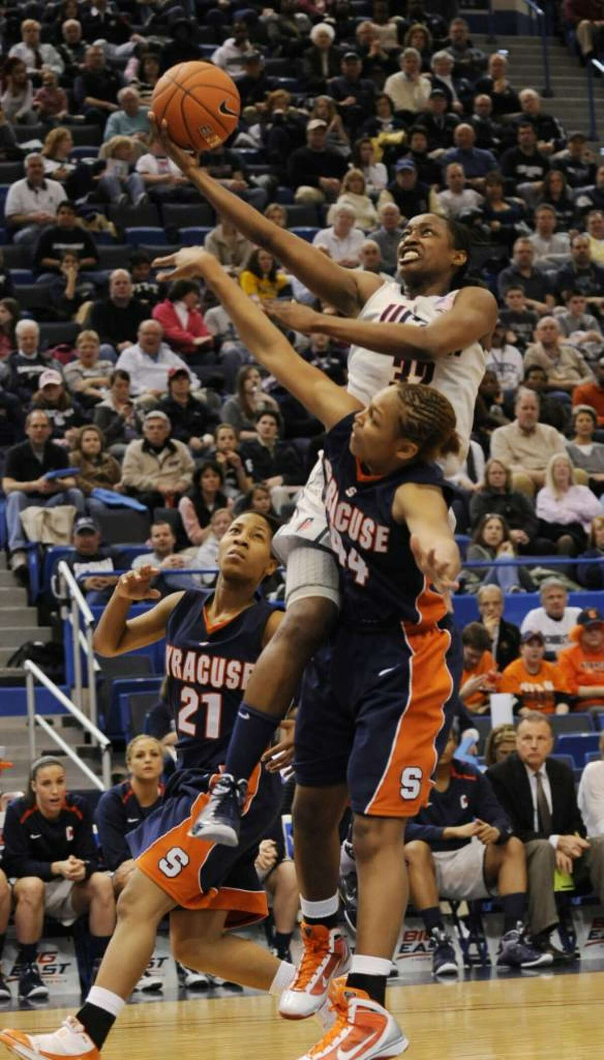 Connecticut's Kalana Greene goes up for a shot past Syracuse's Erica Morrow, left, in the second half of an NCAA college Big East Championship quarterfinal women's basketball game in Hartford, Conn., Sunday, March 7, 2010. Connecticut won 77-41. (AP Photo/Bob Child)