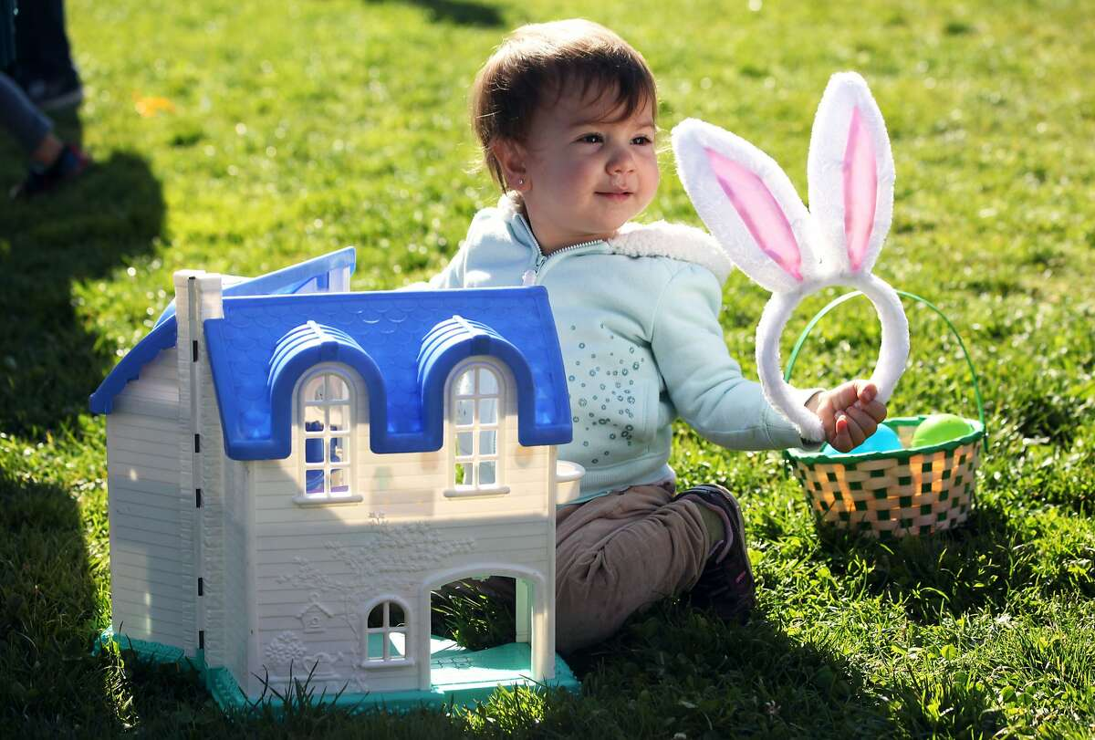 Chloe Samaranch plays with toy house and bunny ears at the annual Easter egg hunt in Duboce Park in San Francisco, Calif., Saturday April 4, 2015.