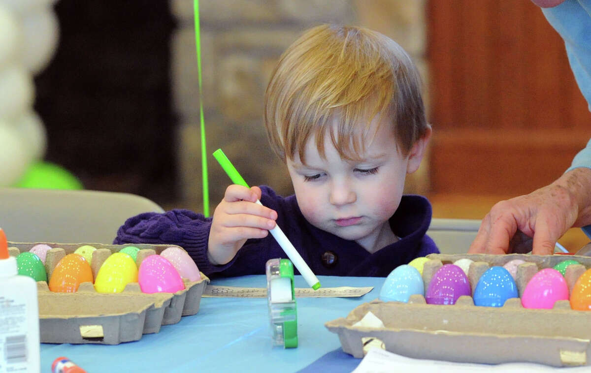 Charlie Wilkinson, 2, makes an Easter decoration during the Family Eggstravaganza arts & crafts activities event for Easter at the Round Hill Community House in Greenwich, Conn., Saturday, April 4, 2015.