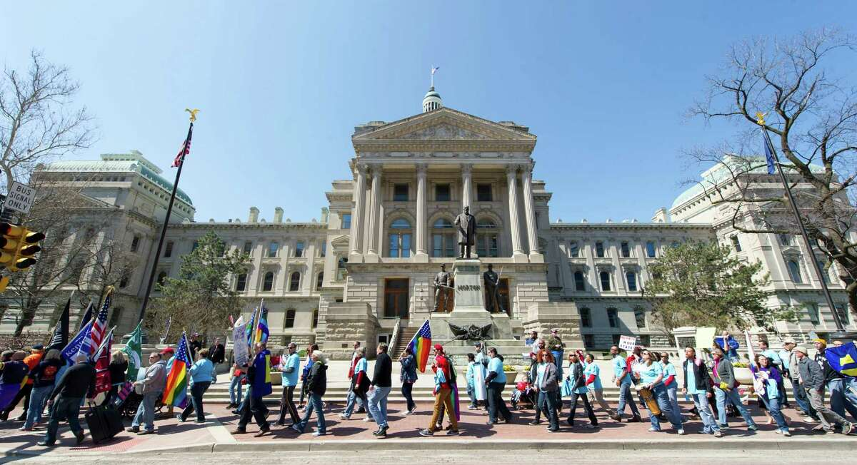 Opponents of Indiana Senate Bill 101, the Religious Freedom Restoration Act, march past the Indiana Statehouse en route to Lucas Oil Stadium in Indianapolis on Saturday, April 4, 2015 to push for a state law that specifically bars discrimination based on sexual orientation or gender identity. (AP Photo/Doug McSchooler)