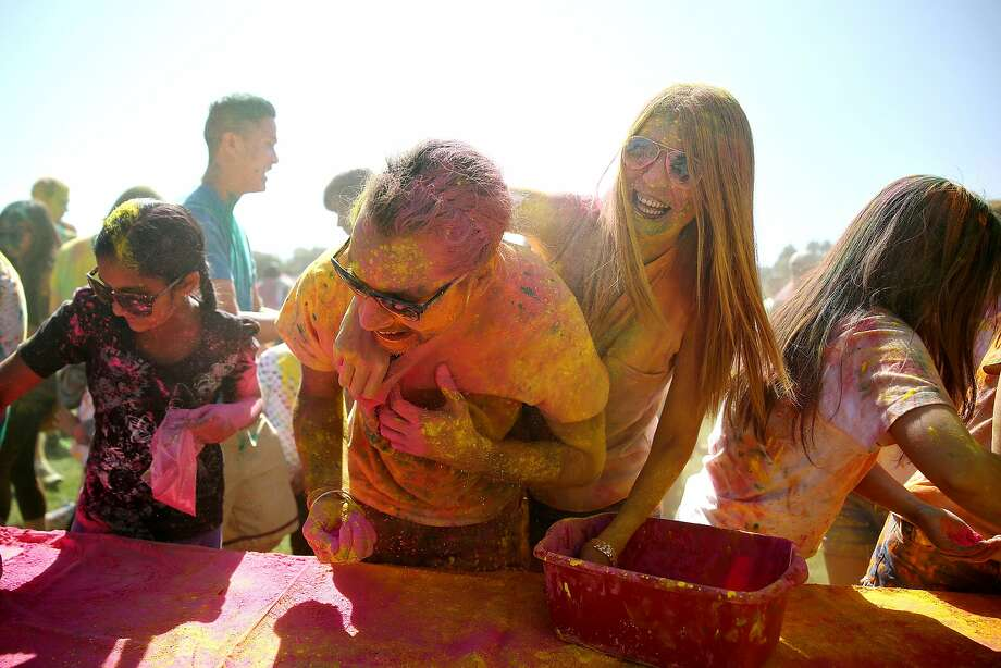 Dilek Oluklu applies color on Sahajit Saluja from Sunnyvale during the Holi celebration at Sandhill Fields on Saturday, April 4 in Stanford University, CA. The event was organized by volunteer run non profit, Asha for Education, which funds literacy projects in India. Photo: Shweta Gulati, Special To The Chronicle