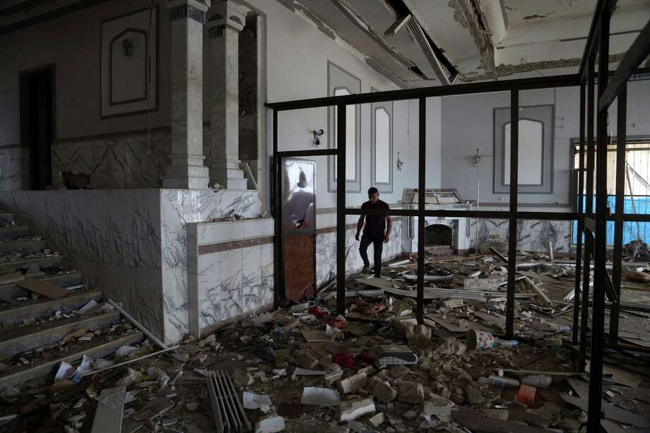 A man inspects one of Saddam Hussein's palaces in Tikrit, 80 miles north of Baghdad, on Iraq. The city has been left in ruins after Islamic State took it over last June and Iraqi troops reclaimed it after an intense fight. Photo: Khalid Mohammed, STF / ASSOCIATED PRESS