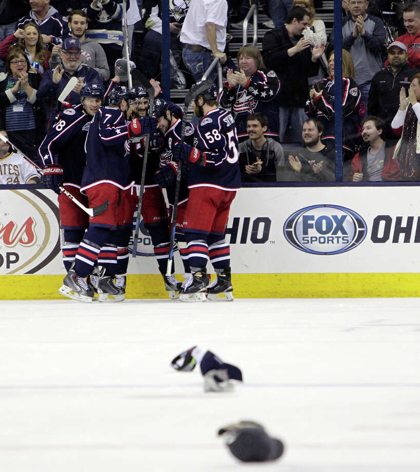 Nick Foligno's is mobbed by his Blue Jackets teammates and showered with caps after completing a hat trick against the Penguins in Columbus, Ohio. Photo: Jay LaPrete / Associated Press / FR52593 AP