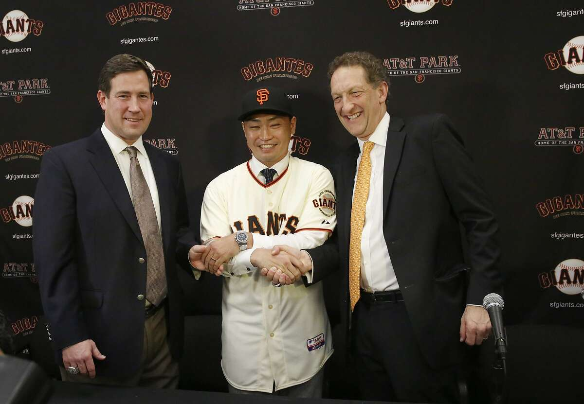 Bobby Evans, Nori Aoki and Larry Baer pose for photos and video after a press conference introducing Aoki to the Giants at AT&T Park Jan. 20, 2015 in San Francisco, Calif.