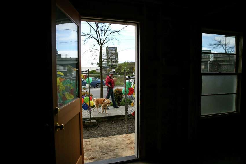 A dog is walked past the former home of Edith Macefield as the house goes up for sale on Tuesday, March 31, 2015 in Seattle's Ballard neighborhood.
