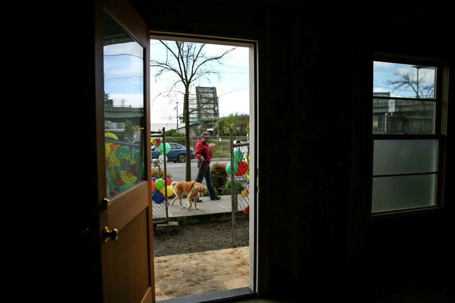 A dog is walked past the former home of Edith Macefield as the house goes up for sale on Tuesday, March 31, 2015 in Seattle's Ballard neighborhood. Photo: JOSHUA TRUJILLO, SEATTLEPI.COM / SEATTLEPI.COM