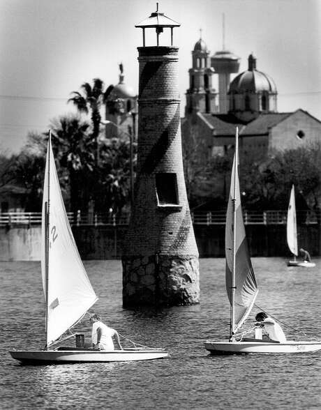 Sailboats pass the miniature lighthouse at Woodlawn Lake, where the Tower of the Americas and Basilica of the National Shrine of the Little Flower are seen in the distance in 1993. The lake, built in 1888, is said to have once covered over twice its current 30 acres. File Photo Photo: JOHN DAVENPORT,  STAFF / SAN ANTONIO EXPRESS NEWS / SAN ANTONIO EXPRESS NEWS
