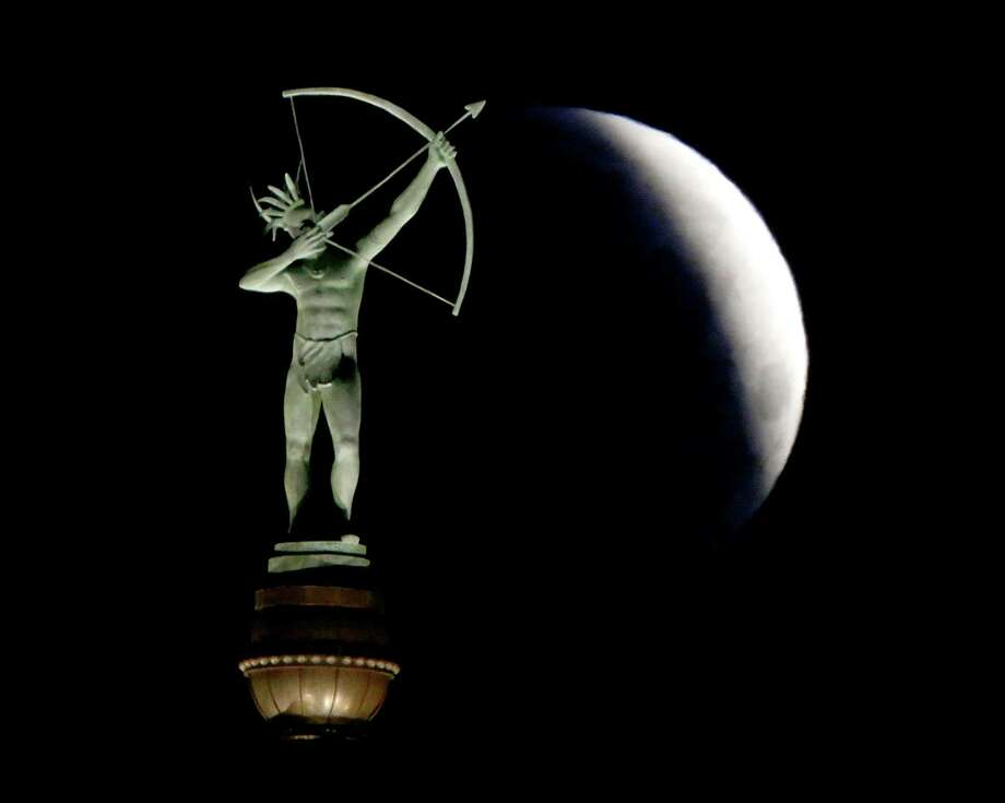 A partially eclipsed full moon sets behind a statue of a Kansa Indian on Saturday at the Kansas Statehouse in Topeka. The moon, NASA engineers say, is attractive as a stepping stone to a manned Mars mission politically, economically and in terms of flexibility. Photo: Charlie Riedel, STF / AP
