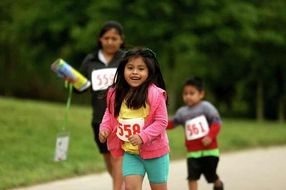Areli Valdez, joins in the B.O.U.N.C.E 5k fun run and walk at the Houston Parks Board Bayou Greenway Greenday on Saturday.