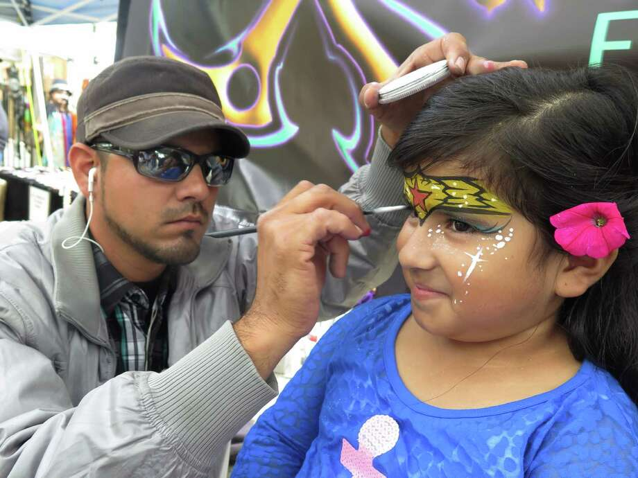 Abigail Delgadillo has her face painted by artist Manuel Salazar at the Starving Artist show at La Villita on Saturday, April 4, 2015. The show has been held yearly since 1963. The event is a fundraiser for the Little Church of La Villita's food pantry program. Photo: Billy Calzada, San Antonio Express-News /  San Antonio Express-News