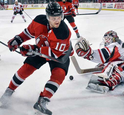Albany Devils' #10 Rod Pelley, left, has his shot stopped by Binghamton Senators' goalie #31 Peter Mannino during Saturday's game at the Times Union Center April 4, 2015 in Albany, NY.  (John Carl D'Annibale / Times Union) Photo: John Carl D'Annibale / 00030124R