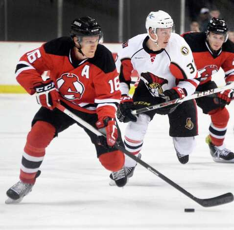 Albany Devils' #16 Chris McKelvie, left, controls the puck followed by Binghamton Senators' #37 Darren Kramer and teammate Cam Janssen, right, during Saturday's game at the Times Union Center April 4, 2015 in Albany, NY.  (John Carl D'Annibale / Times Union) Photo: John Carl D'Annibale / 00030124R