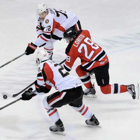 Albany Devils' #28 Matt Lorito, blasts through Binghamton Senators' #20 Alex Grant, bottom, and #72 AaronJohnson, top, during Saturday's game at the Times Union Center April 4, 2015 in Albany, NY.  (John Carl D'Annibale / Times Union) Photo: John Carl D'Annibale / 00030124R