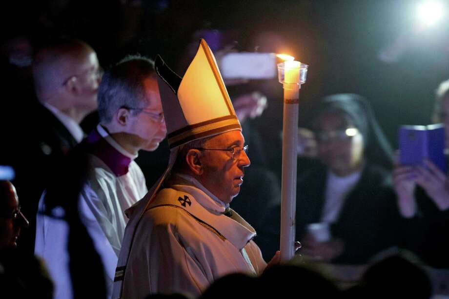 Pope Francis holds a lit white candle as he arrives for an Easter vigil service, in St. Peter's Basilica, at the Vatican, Saturday, April 4, 2015. (AP Photo/Andrew Medichini) Photo: Andrew Medichini, STF / AP