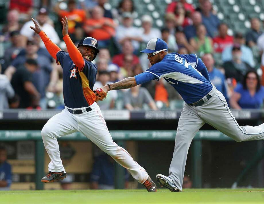 Ruben Sosa, left, is tagged out by Royals shortstop Gabriel Noriega after being caught in a rundown between third and home in the seventh inning of Saturday's final exhibition game at Minute Maid Park. Photo: Karen Warren, Staff / © 2015 Houston Chronicle