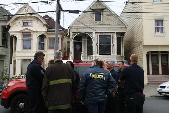 Emergency crews collaborate outside a home near 4th and Lake Street in the Richmond District of San Francisco, Calif. after a body was reported inside the house  Saturday, April 4, 2015.