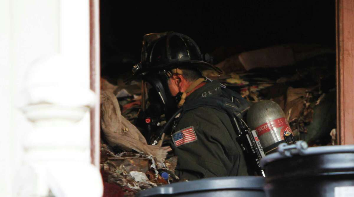 Firefighters search among mounds of trash inside a home where a body was reportedly dead inside near 4th and Lake Street in the Richmond District of San Francisco, Calif. Saturday, April 4, 2015.