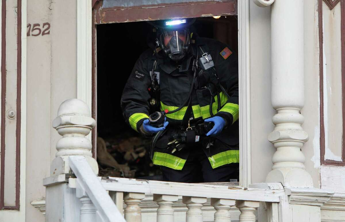 A firefighter emerges from a home where a body was found near 4th and Lake Street in the Richmond District of San Francisco, Calif. Saturday, April 4, 2015.