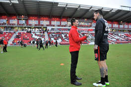 Scorpions coach Alen Marcina talks with player Eric Hassli before the 2015 spring season opener against the Tampa Bay Rowdies.