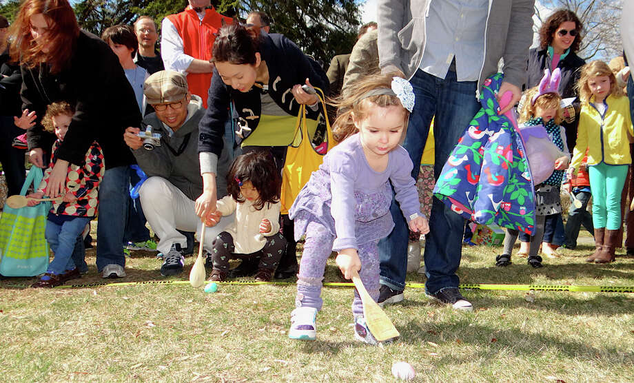 Finley Havens, 2, of Westport pushes an Easter egg across the Great Lawn of the Pequot Library at the annual egg roll Saturday. Photo: Mike Lauterborn / Fairfield Citizen