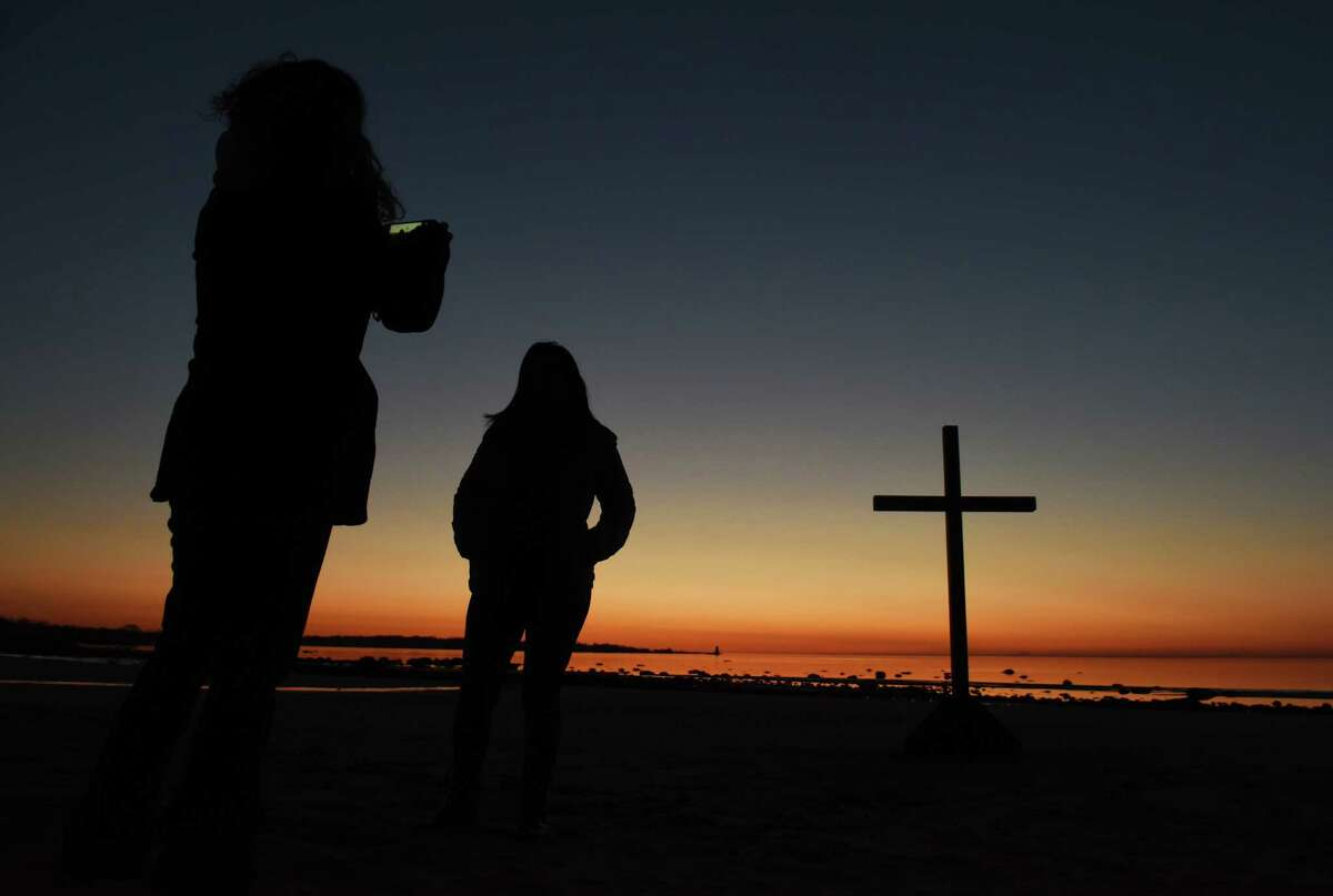 Milena Ramirez, left, of Byram, takes a photo of Sonia Goncalves, of Greenwich, as the sun rises on the beach before the First Congregational Church of Greenwich Easter sunrise at Greenwich Point Park in Old Greenwich, Conn. Sunday, April 5, 2015. Over 100 people observed the service to pray, sing hymns and read scripture as the sun rose on the beach.
