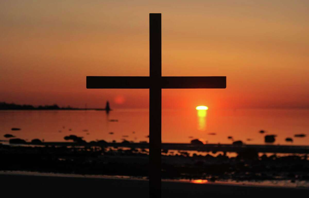 The sun rises in front of a cross on the beach during the First Congregational Church of Greenwich Easter sunrise service at Greenwich Point Park in Old Greenwich, Conn. Sunday, April 5, 2015. Over 100 people observed the service to pray, sing hymns and read scripture as the sun rose on the beach.