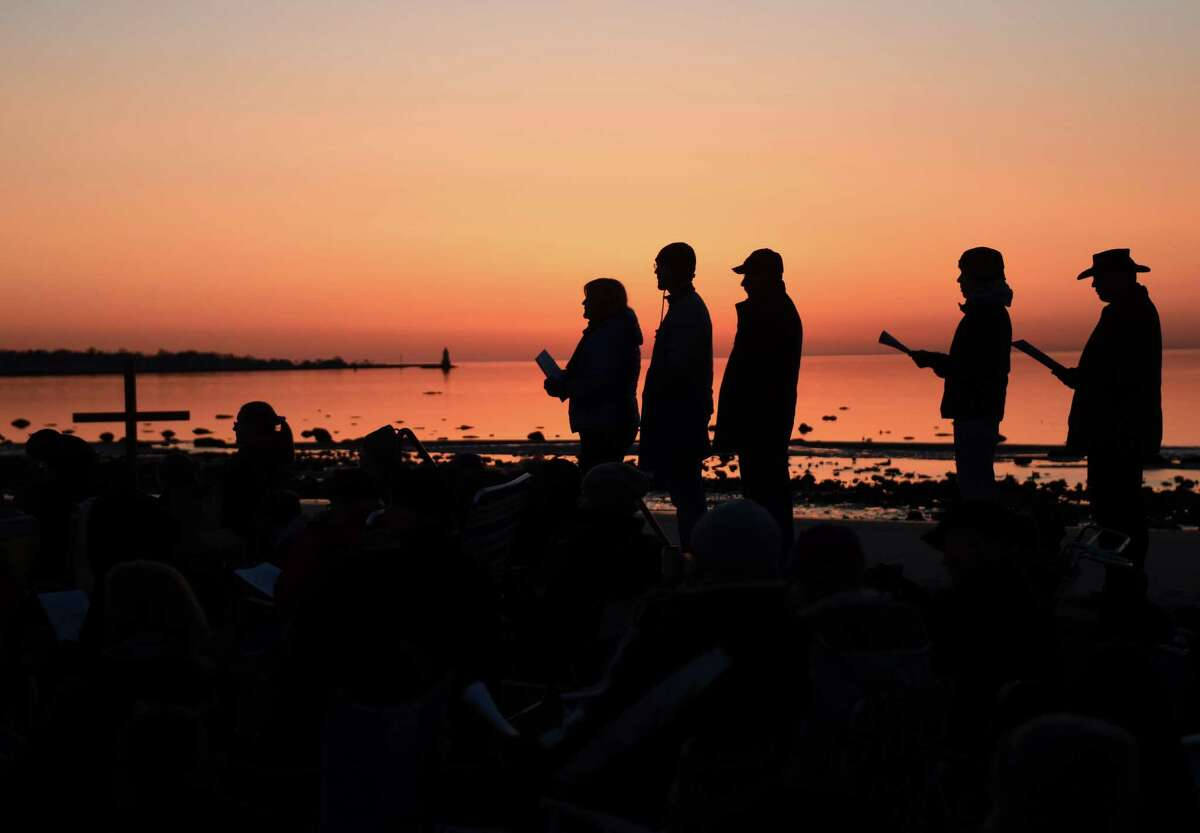 Folks sing hymns as the sun rises on the beach during the First Congregational Church of Greenwich Easter sunrise service at Greenwich Point Park in Old Greenwich, Conn. Sunday, April 5, 2015. Over 100 people observed the service to pray, sing hymns and read scripture as the sun rose on the beach.