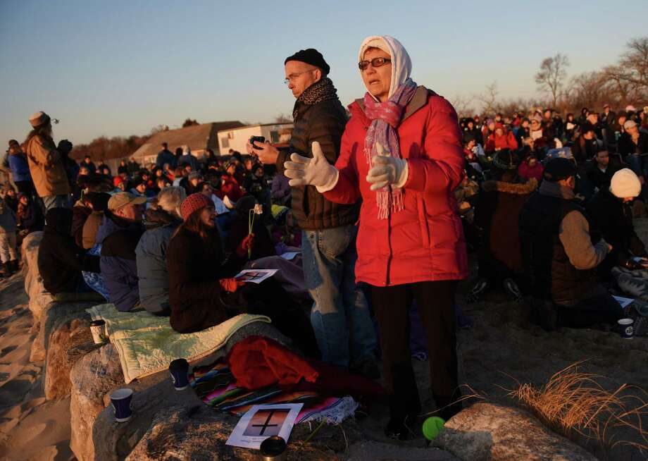 Dorothy Mueller, of Stamford, claps during a song at the First Congregational Church of Greenwich Easter sunrise service on the beach at Greenwich Point Park in Old Greenwich, Conn. Sunday, April 5, 2015.  Over 100 people observed the service to pray, sing hymns and read scripture as the sun rose on the beach. Photo: Tyler Sizemore / Greenwich Time