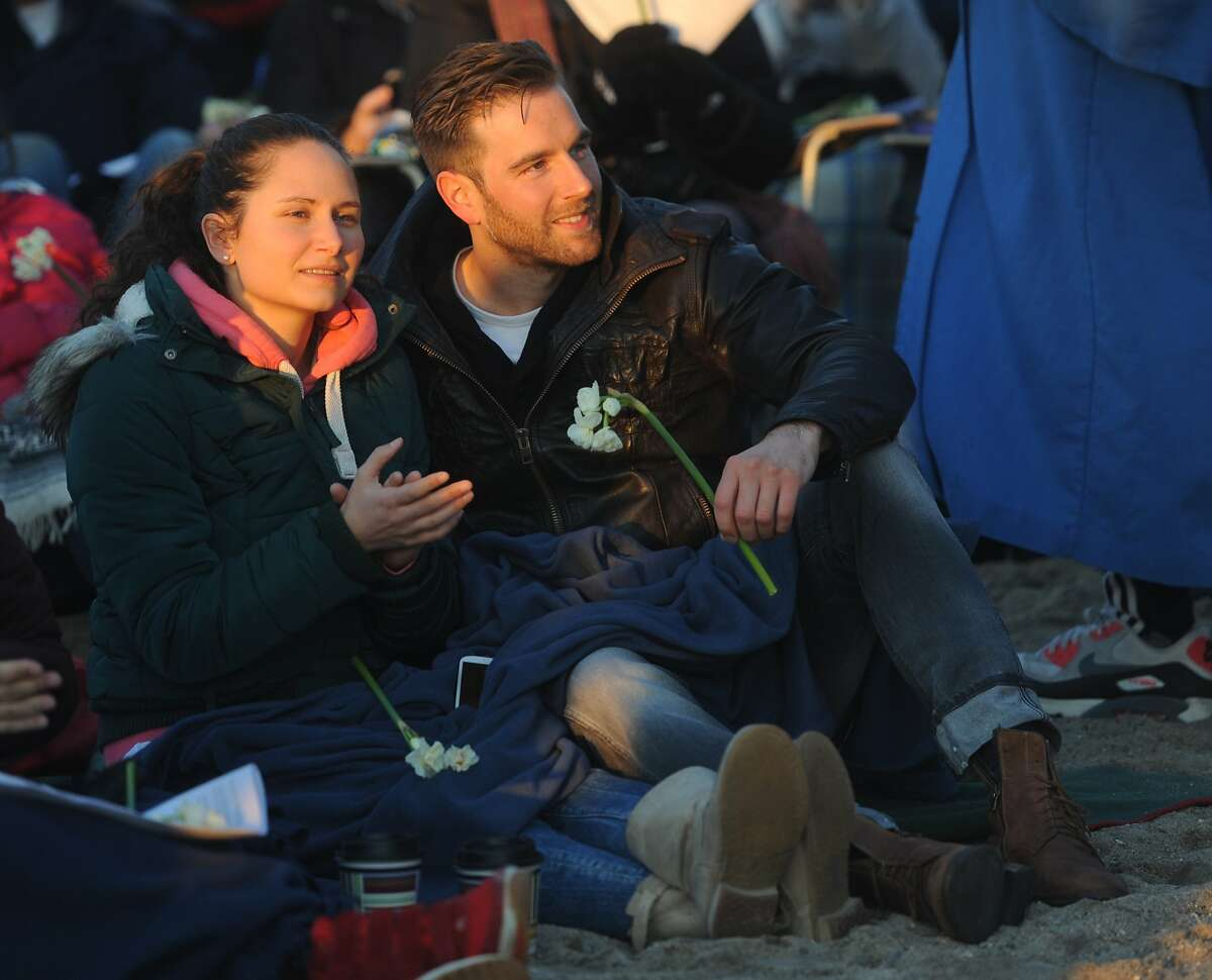 Visiting from Munich, Germany, Vanessa Pfetsch and Henrik Schlichting watch the First Congregational Church of Greenwich Easter sunrise service on the beach at Greenwich Point Park in Old Greenwich, Conn. Sunday, April 5, 2015. Over 100 people observed the service to pray, sing hymns and read scripture as the sun rose on the beach.