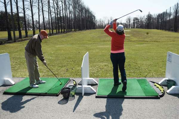 Alan Grubel, of White Plains, N.Y., and Kathy Sheinhouse practice their swings on the driving range at the Griffith E. Harris Golf Course in Greenwich, Conn. Sunday, April 5, 2015. The course opened for the season on Saturday and attracted lots of eager golfers on Sunday with the beautiful weather.