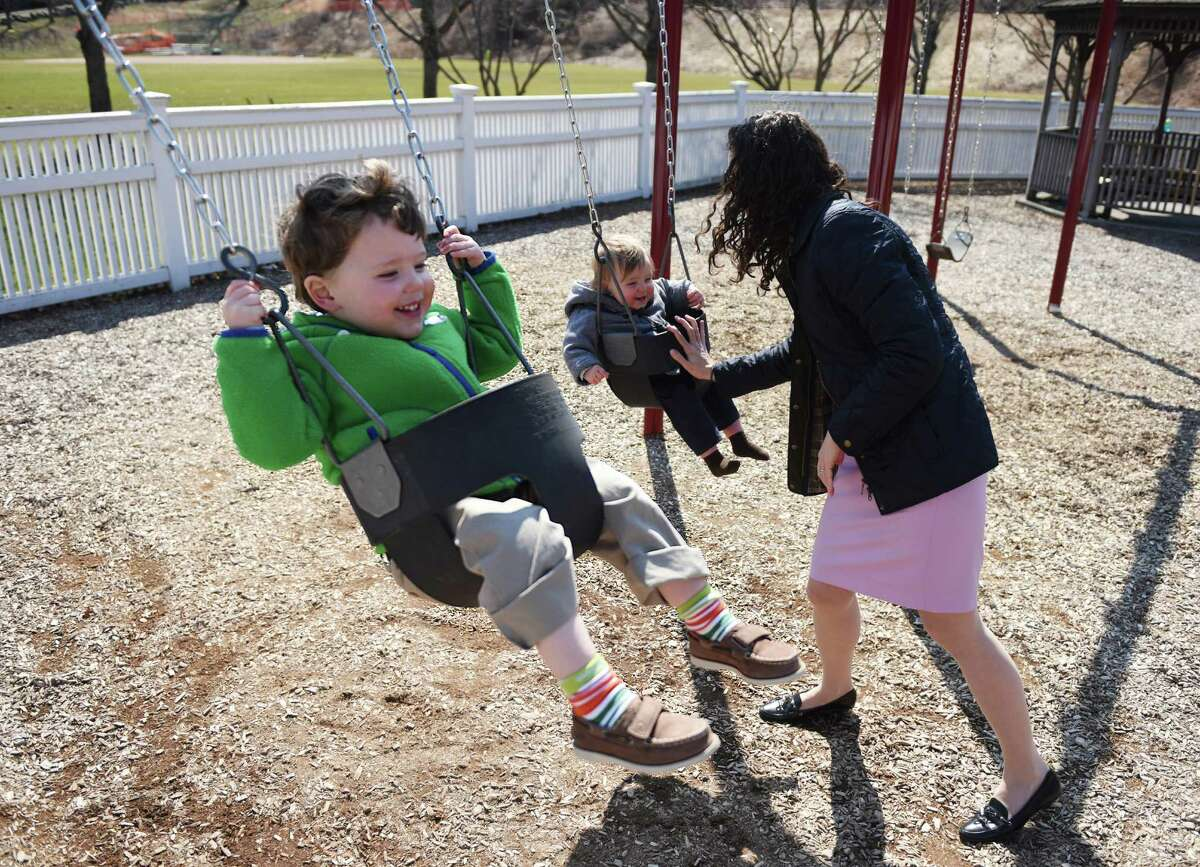 Julie Lorig, of Glenville, pushes her sons Brian, left, 2, and Timothy, 1, on swings at the Western Greenwich Civic Center Park in the Glenville section of Greenwich, Conn. Sunday, April 5, 2015. Sunday's high temperature reached the upper-50s and area parks were full of activity.