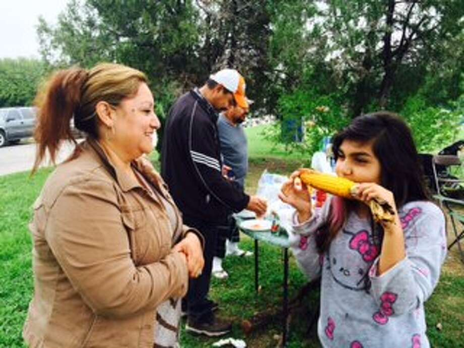 : Maria Garcia, 42, of San Antonio, laughs as her daughter, Jemmelyn Garcia, 9, eats grilled corn on the cob during the family's camping trip in Woodlawn Lake Park. Many families camp at the park overnight during the Easter weekend. The site is far less crowded than Brackenridge Park. Photo: By Peggy