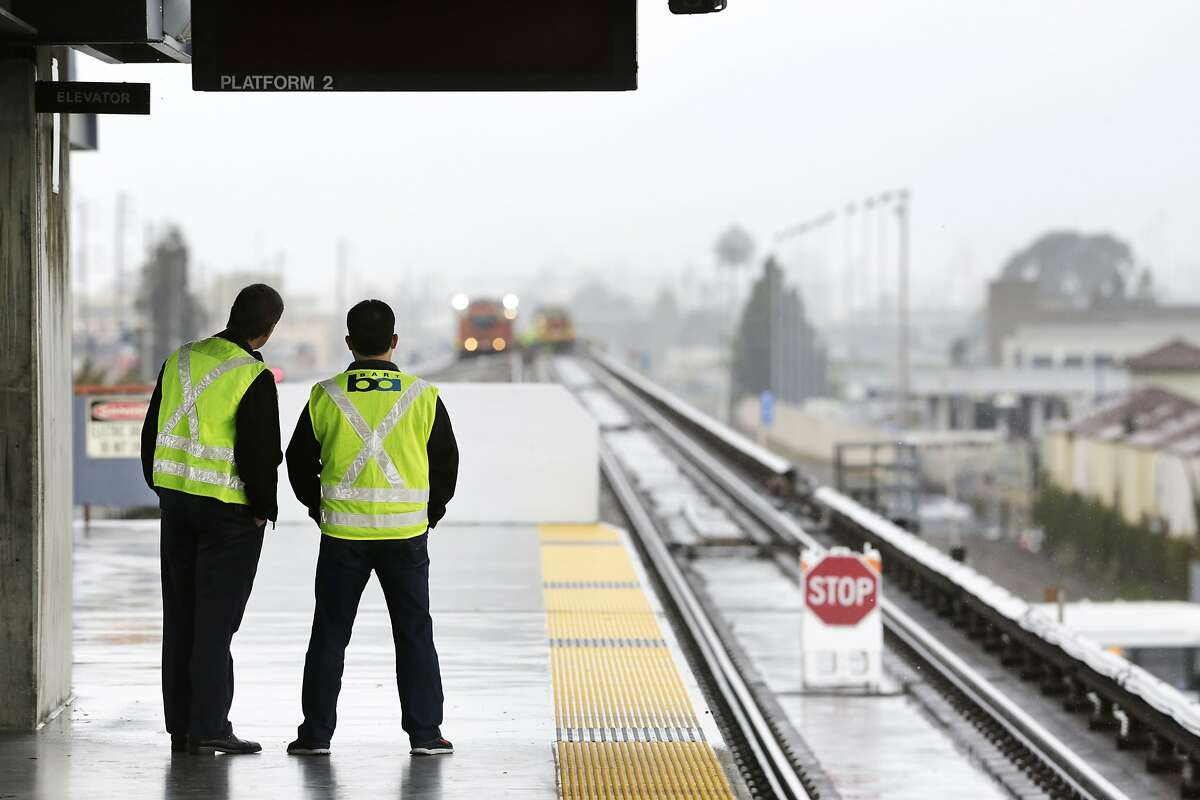 BART Manager of Rail Operations Colby Barry (left) and Chief Transportation Officer Roy Aguilera watch maintenance work underway beyond the north end of the Coliseum Station platform in Oakland on Sunday, April 5, 2015. A section of track between the Coliseum and Fruitvale stations will be closed on Sundays in the weeks to come while crews replace aging tracks and ties.