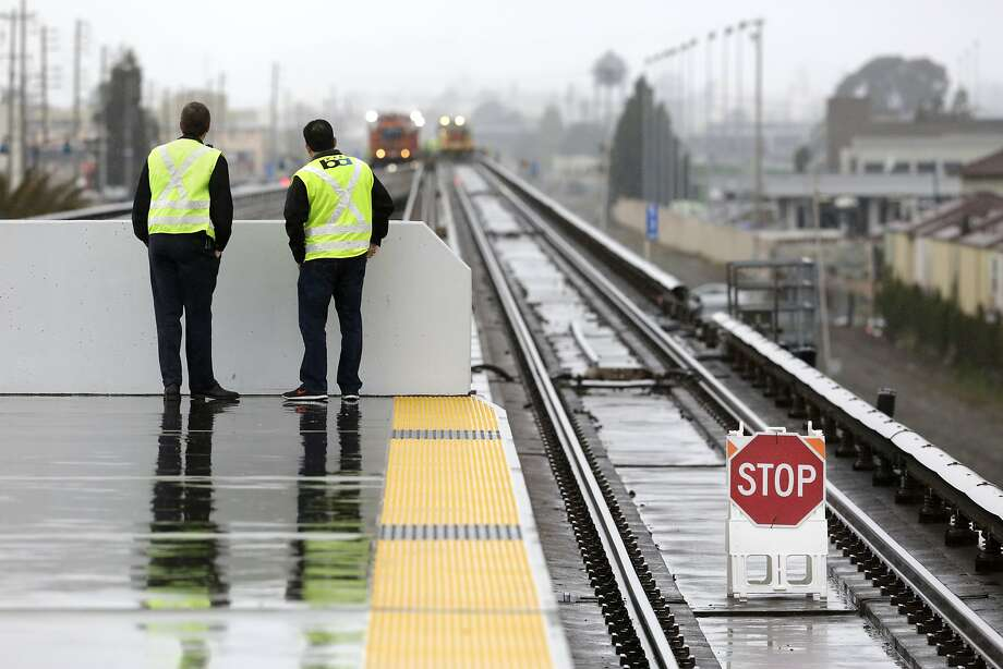 BART Manager of Rail Operations Colby Barry (left) and Chief Transportation Officer Roy Aguilera watch maintenance work underway beyond the north end of the Coliseum Station platform in Oakland on Sunday, April 5, 2015. A section of track between the Coliseum and Fruitvale stations will be closed on Sundays in the weeks to come while crews replace aging tracks and ties. Photo: Terray Sylvester, The Chronicle