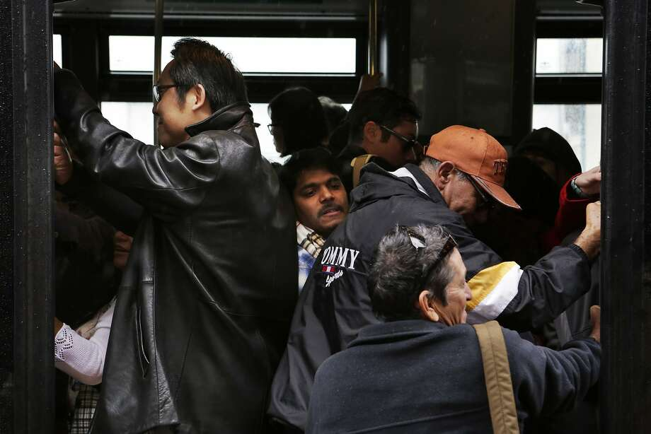Passengers squeeze onto an AC Transit shuttle at the Coliseum BART Station in Oakland on Sunday, April 5, 2015. A section of track between the Coliseum and Fruitvale stations will be closed on Sundays while crews replace aging tracks and ties. AC Transit is offering buses between the two stations during the closures. Photo: Terray Sylvester, The Chronicle